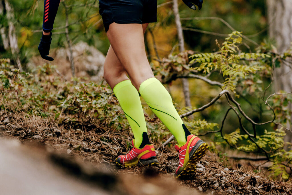 female runner in yellow compression socks running forest trail